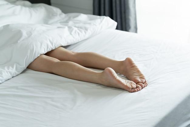 Hoogste mening van de benen van een slanke vrouw. naakte benen van een jonge vrouwenslaap op haar bed thuis.