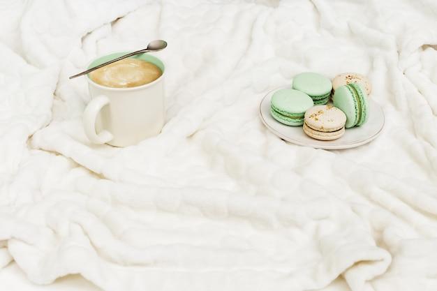 Hoogste mening van de cappuccino van de kopkoffie met smakelijke makarons op zachte witte bontoppervlakte. warm drankje met melk en dessert. winterochtend concept.