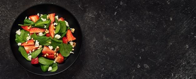 Hoogste mening van de gezonde salade van de aardbeispinazie op zwarte achtergrond
