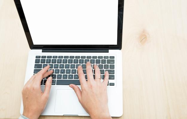 Hoogste mening van de hand van de persoon het typen op laptop over de houten achtergrond