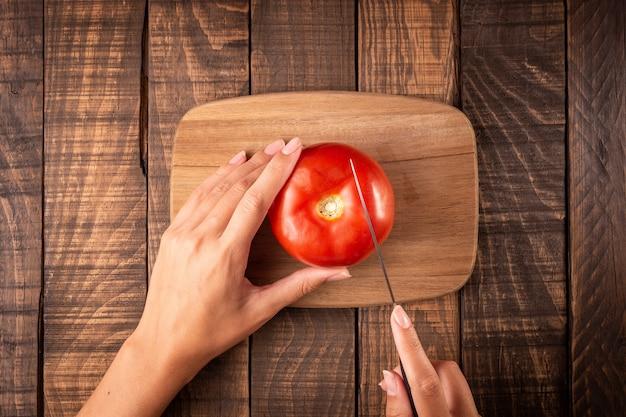Hoogste mening van de handen die van een vrouw met een mes een tomaat op een raad op een houten lijst snijden