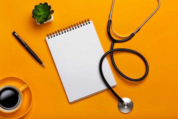 Hoogste mening van de lijst van een arts met blocnote en penstethoscoop, toetsenbord, voorschrift en pillen, een kop van koffie op een gele achtergrond