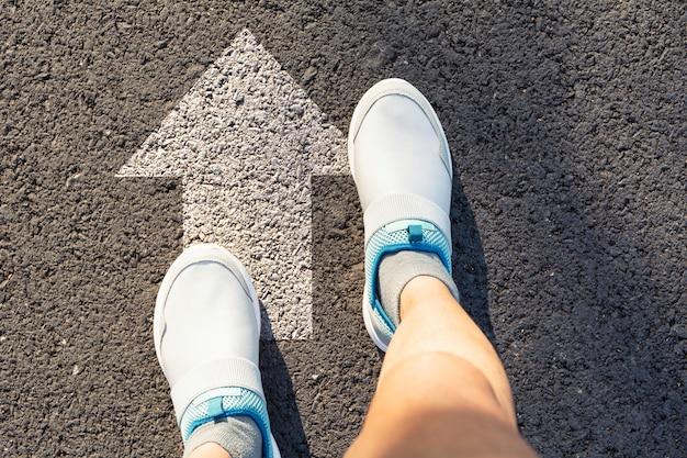 Hoogste mening van de mens die witte schoenen draagt die een manier kiezen duidelijk met witte pijlen