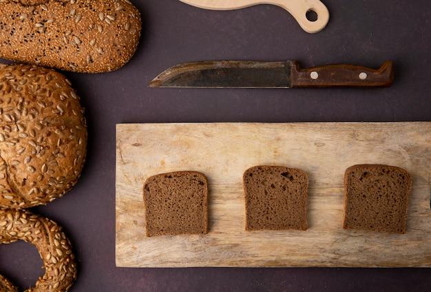 Hoogste mening van de plakken van het roggebrood op scherpe raad met rond brood en mes op kastanjebruine achtergrond