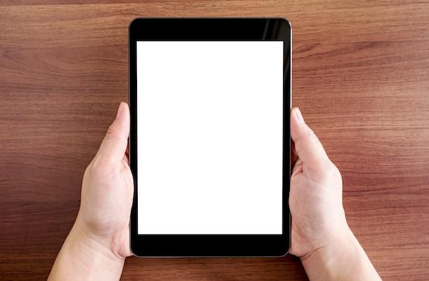 Hoogste mening van de tablet van de twee handholding met het lege witte scherm op donkere bruine houten lijstbovenkant