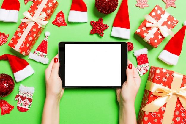 Hoogste mening van de tablet van de vrouwenholding in haar handen op groen gemaakt van kerstmisdecoratie.