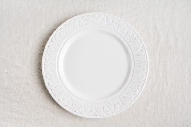 Hoogste mening van de witte lege ceramische plaat op linnentafelkleed met exemplaarruimte. concept eten tafel serveren.
