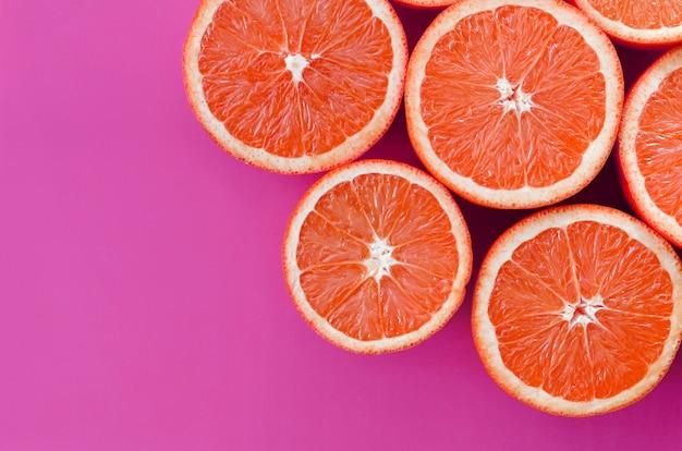 Hoogste mening van diverse grapefruitplakken op heldere achtergrond in purpere kleur.