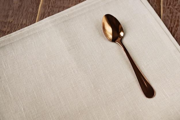 Hoogste mening van doekservet van beige kleur en gediende theelepel op houten lijst.