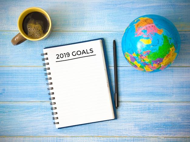 Hoogste mening van doelstellingen 2019 van het notitieboekjekantoor jaar op blauwe houten lijst.