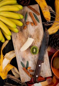 Hoogste mening van een bos van banaanfruit en gesneden banaan op een houten scherpe raad met een mes en pijpjes kaneel op plattelander