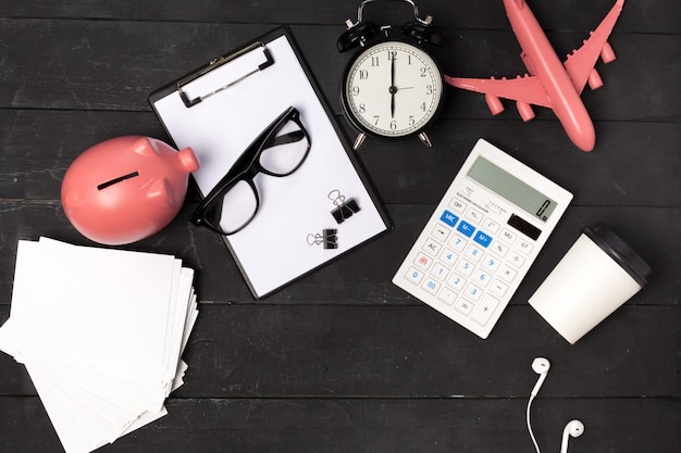 Hoogste mening van een bureaulijst met kantoorbehoeften en roze vliegtuig