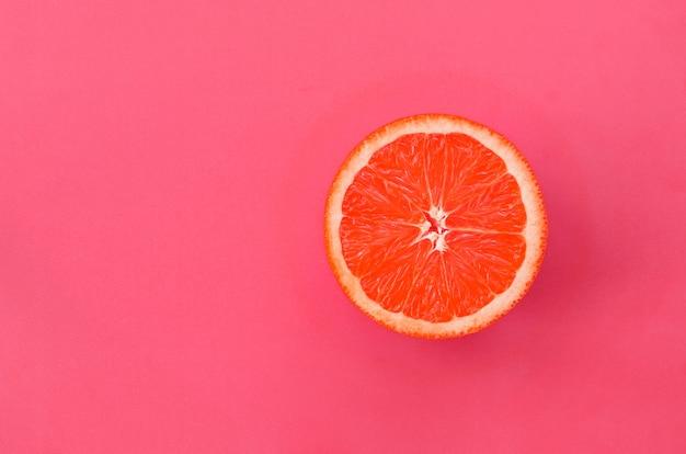 Hoogste mening van een één grapefruitplak op heldere achtergrond in lichtrose kleur.