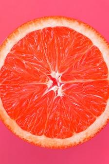 Hoogste mening van een één grapefruitplak op heldere achtergrond in lichtrose kleur