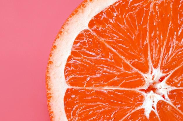 Hoogste mening van een één grapefruitplak op heldere achtergrond in lichtrose