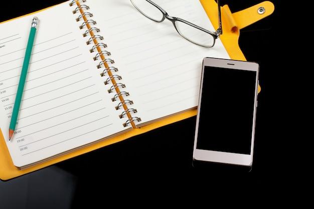 Hoogste mening van een open notaboek, glazen, pen en smartphone op een zwarte achtergrond.