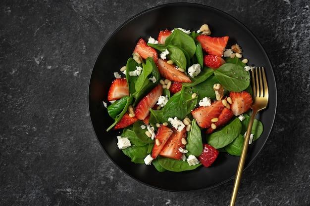 Hoogste mening van een plaat met de salade van de aardbeispinazie op zwarte achtergrond