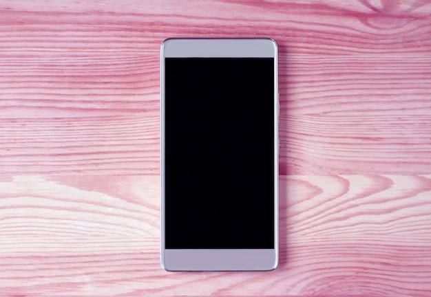 Hoogste mening van een smartphone met het lege scherm op roze houten lijst met vrije ruimte voor tekst en ontwerp