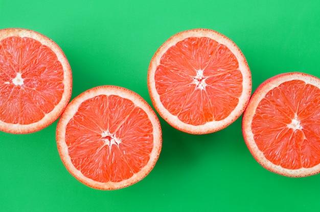 Hoogste mening van een verscheidene grapefruitplakken op heldere achtergrond in groene kleur