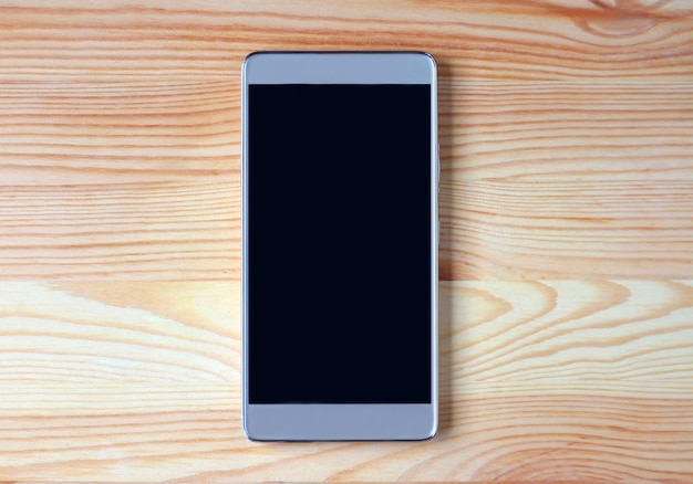 Hoogste mening van een zwarte lege het schermsmartphone die op lichtbruine houten lijst wordt geïsoleerd