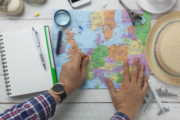 Hoogste mening van essentiële punten voor reis en technologieachtergrond concept boven de de holdingskop thee van de handmens met verscheidene toebehoren voor reiziger treft voorbereidingen om op reis en vakantie te gaan object op modern hout