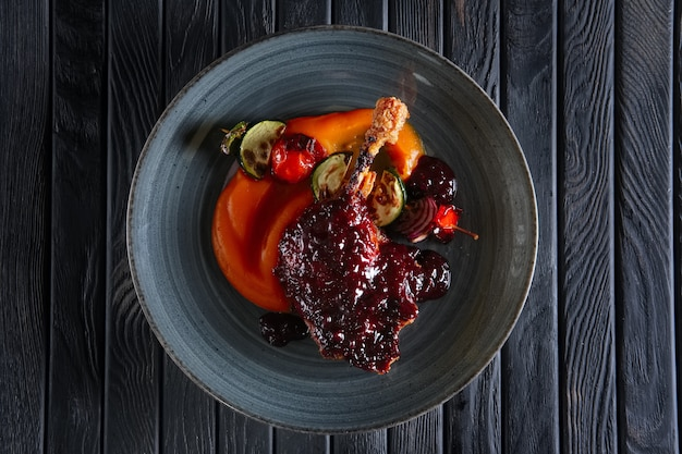 Hoogste mening van gebraden eenddij met wortelpuree en zuccini, peper en ui op houten vleespen