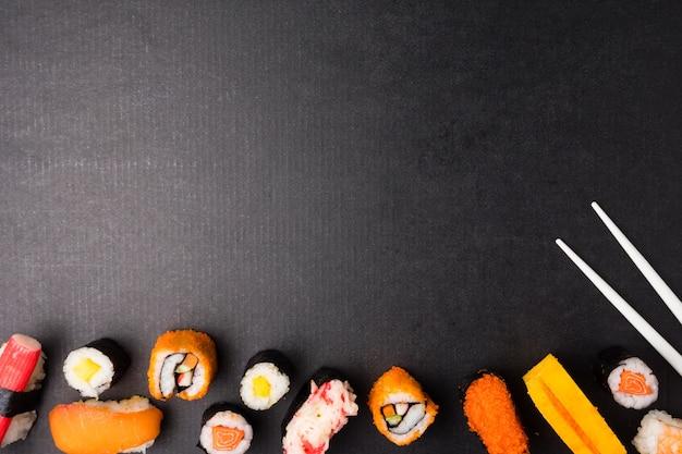 Hoogste mening van geplaatste sushi en eetstokjes op zwarte achtergrond, japans voedsel.