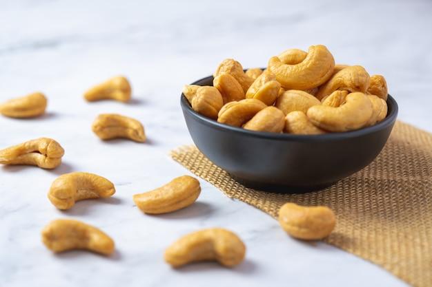 Hoogste mening van geroosterde cashewnoot in zout in zwarte kom op witte marmeren vloer