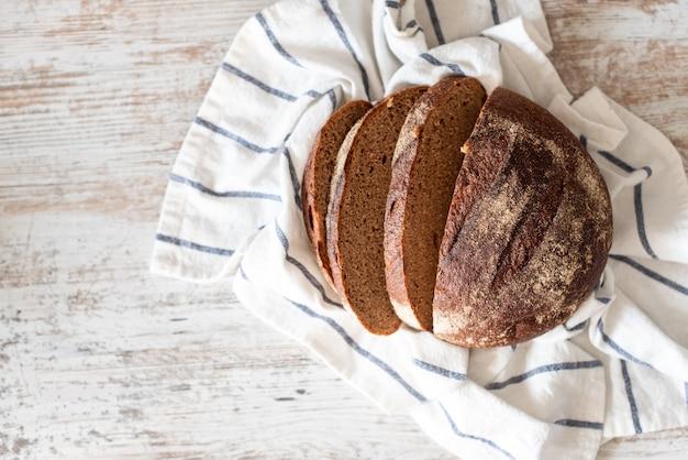 Hoogste mening van gesneden volkorenbrood op donkere ructische houten close-up als achtergrond