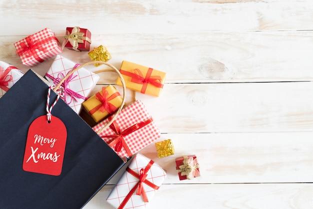 Hoogste mening van giftdoos en rode het winkelen zak met berichtmarkering op een houten witte achtergrond.