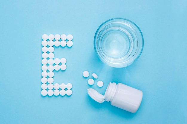 Hoogste mening van glas water en container met pillen die brief e spellen