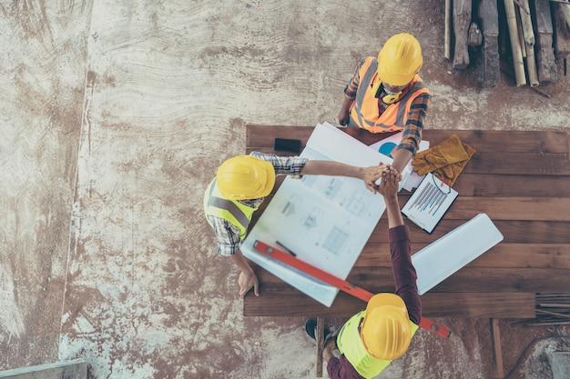 Hoogste mening van glimlachende bouwers en architecten in bouwvakkers die hoge vijf in bouwwerfvloer maken bij fabriek, gebaar en mensenconcept.