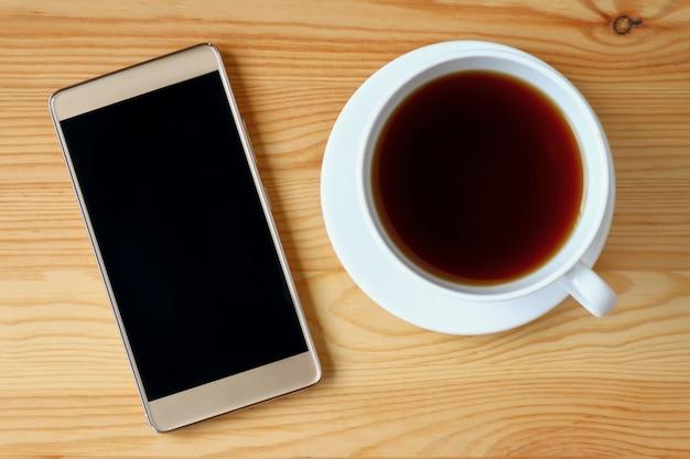 Hoogste mening van gouden smartphone met een kop van hete thee op houten lijst