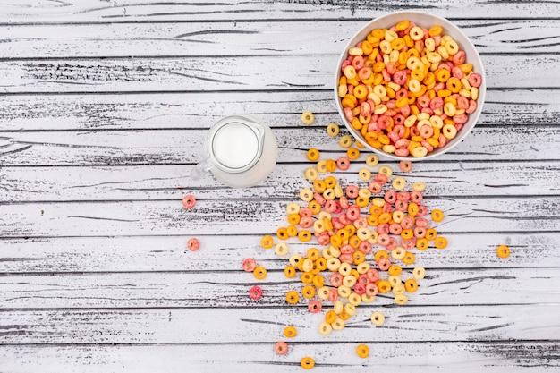 Hoogste mening van graanringen met melk en exemplaarruimte op witte houten horizontale achtergrond
