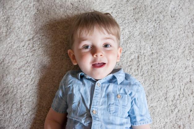 Hoogste mening van grappig klein jong geitje die op de tapijtvloer thuis glimlachen.