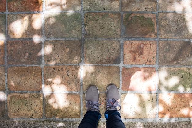 Hoogste mening van grijze tennisschoenen die zich op concrete vloer bevinden.