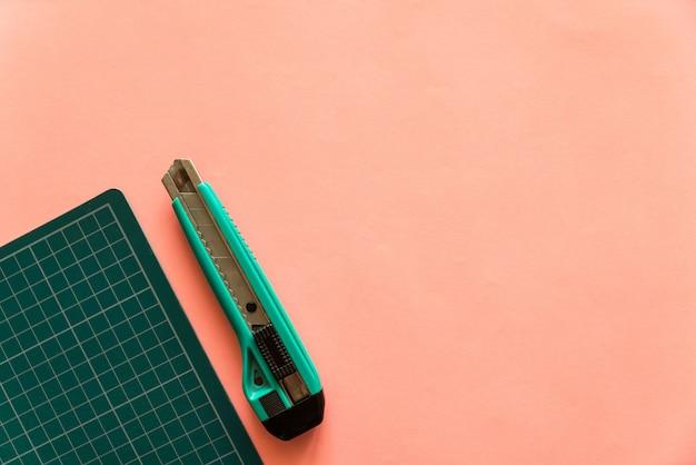 Hoogste mening van groene rubber scherpe mat met groene snijder aan de linkerkant over roze kleurendocument achtergrond. achtergrond met kopie ruimte.