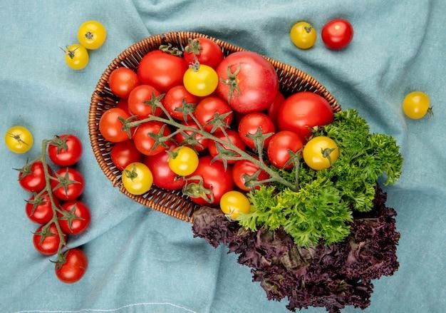 Hoogste mening van groenten als basilicum van de tomatenkoriander in mand met tomaten op blauwe doekoppervlakte