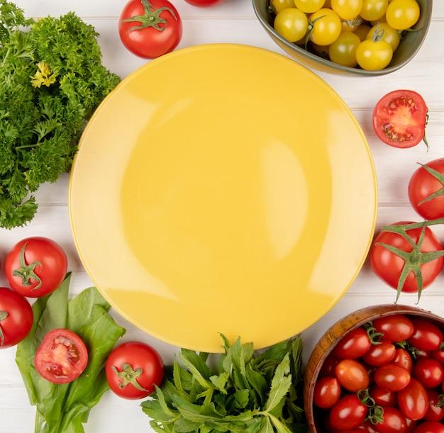 Hoogste mening van groenten als bladeren van de de spinazie de groene munt van de koriandertomaat met lege plaat op centrum op hout