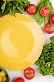 Hoogste mening van groenten als bladeren van de de spinazie de groene munt van de koriandertomaat met lege plaat op hout