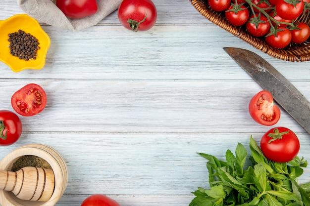 Hoogste mening van groenten als bladeren van de tomaten groene munt met de maalmachine van het zwarte peperknoflook en mes op houten oppervlakte met exemplaarruimte