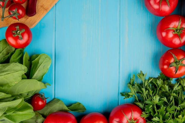 Hoogste mening van groenten als koriander van de spinazietomaat met mes op scherpe raad op blauw met exemplaarruimte