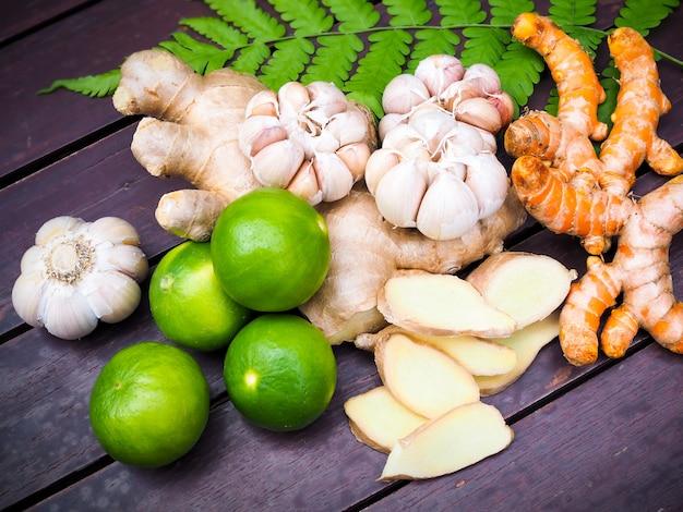 Hoogste mening van groenten en kruiden voor het koken met kurkumawortel, gember, knoflook en citroenfruit op varenbladeren op houten lijst in keuken.