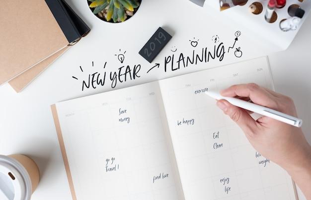Hoogste mening van hand die de planning van het nieuwe jaar op open kalenderontwerper schrijven