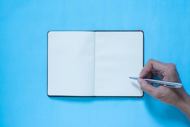 Hoogste mening van hand die op notitieboekje op blauwe en roze pastelkleur bakcground schrijft