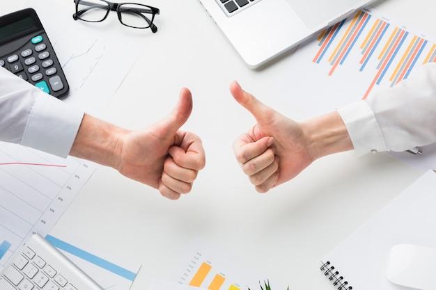 Hoogste mening van handen die duimen over bureau opgeven