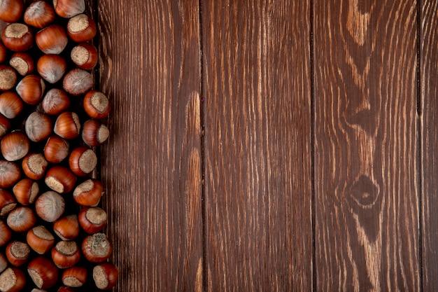 Hoogste mening van hazelnoten in shell die op houten achtergrond met exemplaarruimte wordt verspreid