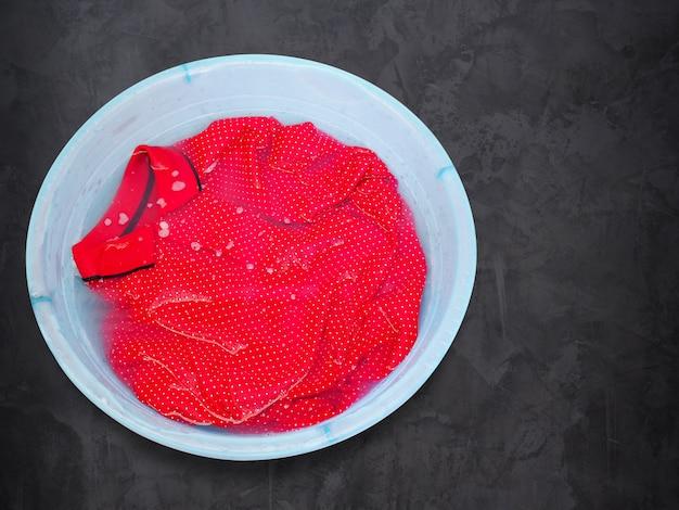 Hoogste mening van het doorweken van wassen rood gekleurd overhemd in ton dat op grijze cementvloer wordt geïsoleerd.