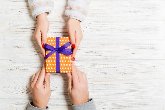 Hoogste mening van het houden van een gift in vrouwelijke en mannelijke handen op houten.