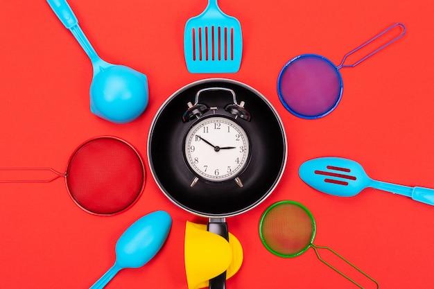 Hoogste mening van het koken werktuigelsamenstelling in keuken die op rode achtergrond wordt geïsoleerd
